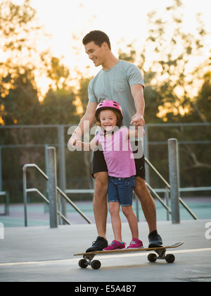 Father and daughter riding skateboard in park
