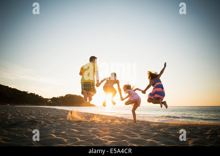 Family jumping for joy on beach