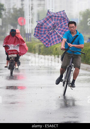 Yangzhou, China's Jiangsu Province. 25th July, 2014. Citizens ride against strong wind in Yangzhou, east China's - Stock Photo
