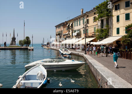 Tourists walking past the harbour in the village of Lazise, on Lake Garda, Italy. - Stock Photo