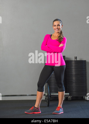Caucasian woman smiling in gym - Stock Photo