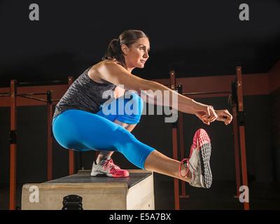 Caucasian woman exercising in gym - Stock Photo
