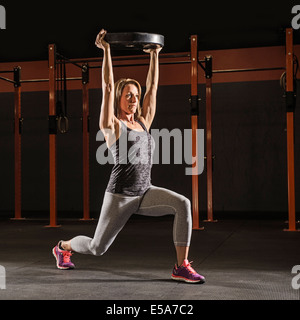 Caucasian woman lifting weights in gym - Stock Photo