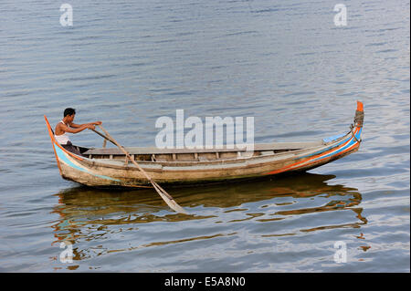 Man in a traditional rowing boat on the Taungthaman Lake, Amarapura, Mandalay Division, Myanmar - Stock Photo