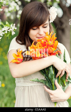 Happy young woman enjoying the fragrance of flowers. Debica, Poland. - Stock Photo