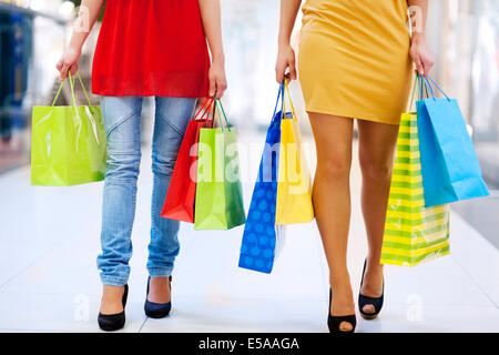 Low angle view of young friends carrying shopping bags. Debica, Poland - Stock Photo