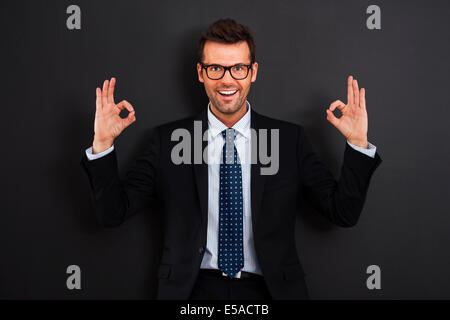 Happy businessman wearing glasses showing OK sign, Debica, Poland - Stock Photo