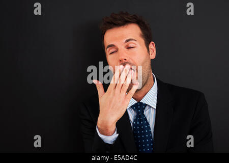 Young businessman yawning and covering his mouth, Debica, Poland - Stock Photo