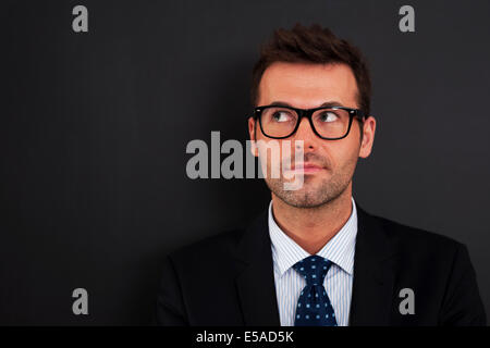 Handsome businessman wearing glasses looking up, Debica, Poland - Stock Photo