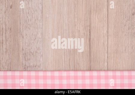 Pink and white checkered cloth on wood as background - Stock Photo