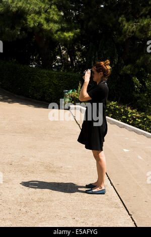Paris, France. 24th July, 2014. Woman in black dress taking pictures with her camera Credit:  Cecilia Colussi/Alamy - Stock Photo