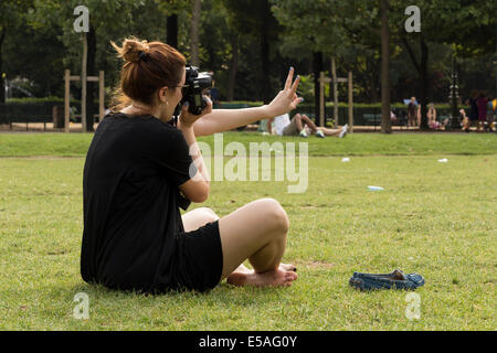 Paris, France. 24th July, 2014. Woman in black dress sitting and taking pictures with her camera Credit:  Cecilia - Stock Photo