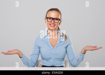 Confident businesswoman welcome gesture, Debica, Poland - Stock Photo