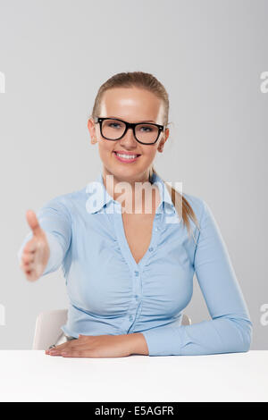 Smiling young businesswoman with welcome hand sign, Debica, Poland - Stock Photo