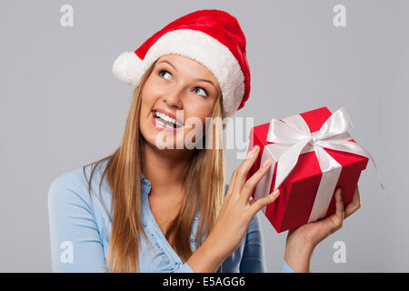 Happy blonde woman holding small red gift, Debica, Poland - Stock Photo