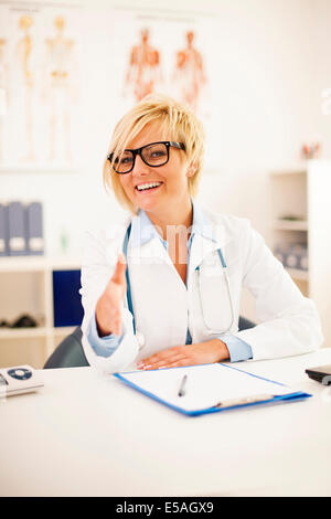 Portrait of smiling female doctor offering a handshake, Debica, Poland - Stock Photo