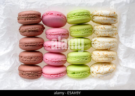 Food: multicolored macarons assortment, arranged on white crumpled paper, isolated on white background - Stock Photo