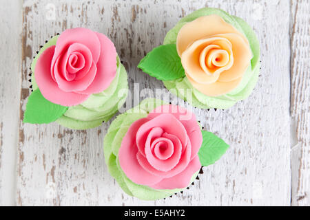 three cupcakes decorated with roses - Stock Photo