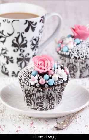 decorated cupcakes with tea in background - Stock Photo