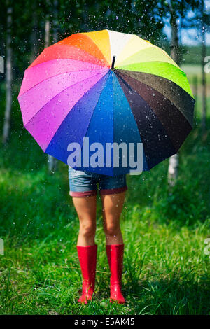 Woman protecting herself from the rain, Debica, Poland. - Stock Photo