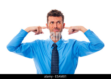 Disgust business man with fingers in ears, Debica, Poland - Stock Photo