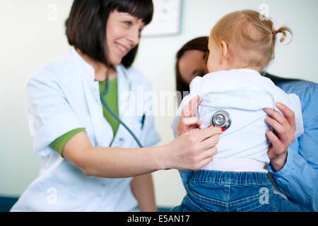 Doctor examining a little girl, Debica, Poland - Stock Photo