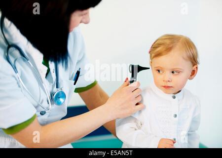 Paediatrician doing ear exam of baby girl, Debica, Poland - Stock Photo