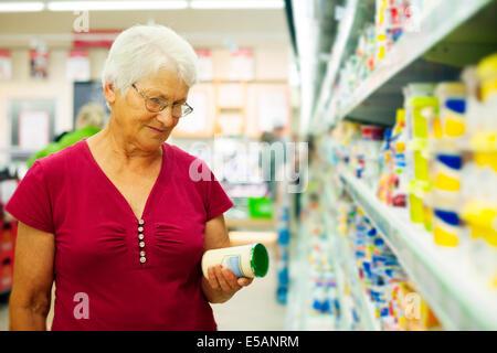 Senior woman checking label on jar Debica, Poland - Stock Photo