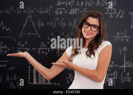 Woman wearing in glasses showing mathematical formulas Debica, Poland - Stock Photo