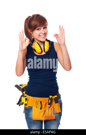 Happy young female construction worker gesturing OK sign Debica, Poland - Stock Photo
