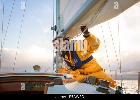 Sailor in yellow foul weather gear checking the lines of the mainsail as he heads into cloudy weather in his sailboat - Stock Photo
