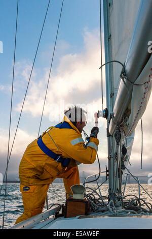 Sailor in yellow foul weather gear securing the halyard after raising the mainsail heading into cloudy weather in - Stock Photo
