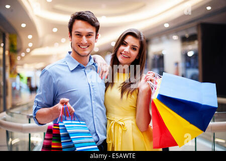 Portrait of happy couple with shopping bags Debica, Poland - Stock Photo