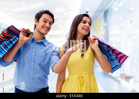 Smiling man showing something woman in the shopping mall Debica, Poland - Stock Photo