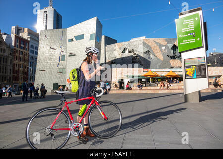 Melbourne Australia Victoria Central Business District CBD Federation Square St. Kilda Road woman teen girl bicycle - Stock Photo