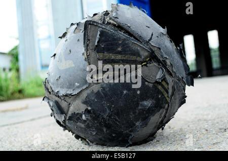 Old football ball badly ragged - Stock Photo