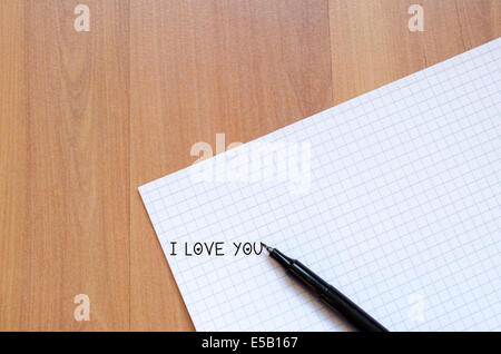 Blank notebook and ink pen on a wooden desk - Stock Photo