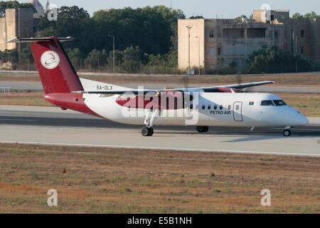 De Havilland Canada Dash 8 turboprop commuter aircraft of the Libyan operator Petro Air on the runway after landing - Stock Photo