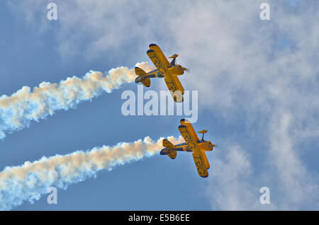 Pair of stunt bi-planes flying inverted against a bright blue sky emitting smoke. - Stock Photo