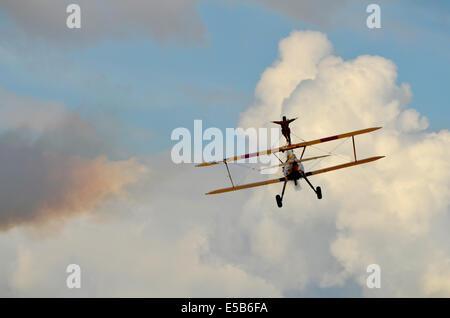 Wing walker on a yellow bi-plane flying away. - Stock Photo