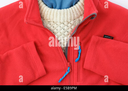Red Polartec fleece jacket with zip open over an Arran sweater for warm winter clothing. England, UK, Britain - Stock Photo