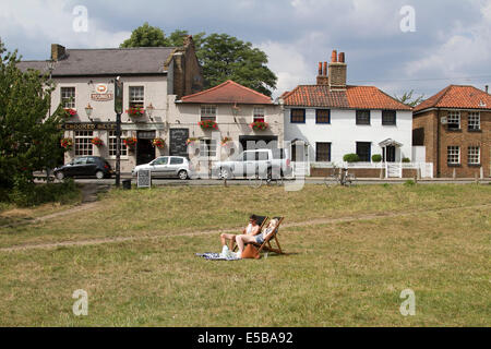 Wimbledon London UK. 26th July 2014. A couple relax in the sunshine on deck chairs outside a pub in Wimbledon Credit: - Stock Photo