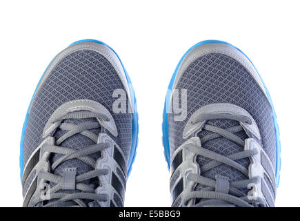 Top view of a pair of silver and blue Adidas running shoes - Stock Photo