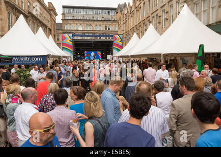 A large group watch a man and woman perform on stage, singing and performing on acoustic guitar, West End Festival, - Stock Photo