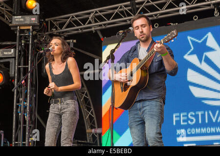 Man and woman perform on stage, singing with acoustic guitar. West End Festival, Glasgow, Scotland, UK, 2014 - Stock Photo