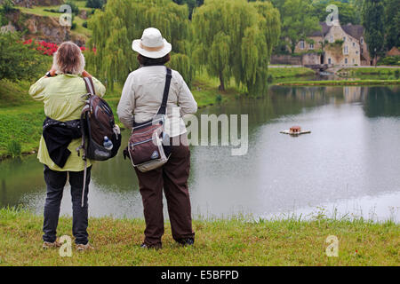 Two woman admiring the views at pond lake by castle Falaise, Calvados, Normandy  in July - Stock Photo