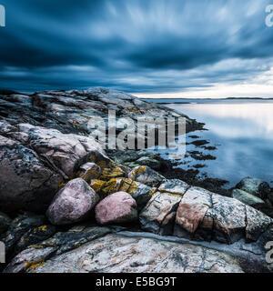 Rocky coastline with dramatic sky - Stock Photo