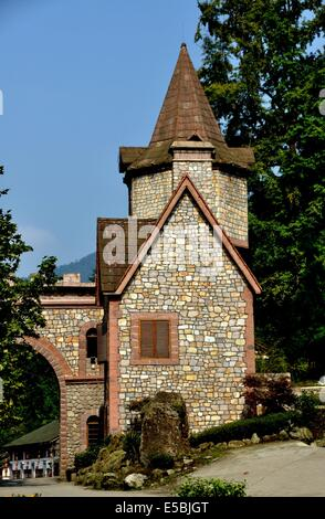 BAI LU TOWN, CHINA:  A French-Swiss style stone gatehouse with turret roof and archway stands at the north entrance - Stock Photo
