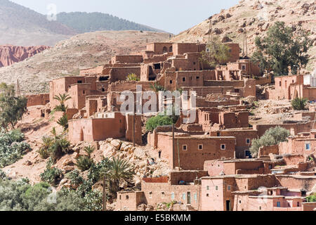 Red brick houses, some ruined, of a Berber village hugging the contours of a hill in the High Atlas Mountains, Morocco - Stock Photo