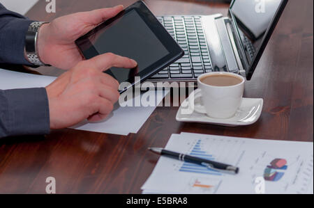 Man works in bussiness office with computer or laptop or notebook and papper graf and he drinks coffee - Stock Photo